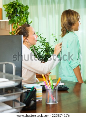 doctor with stethoscope examining teenager boy in office - stock photo