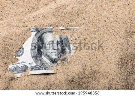 100 dollar bill buried in the sand - stock photo