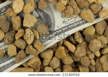 $100 dollar bills under multicolored stones - stock photo