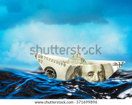 100 dollar paper boat floating on stormy waves - stock photo