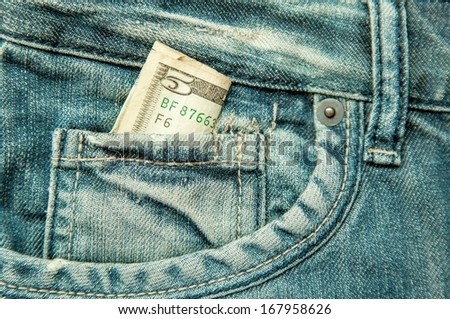 5 dollars banknote in the pocket of jeans - stock photo