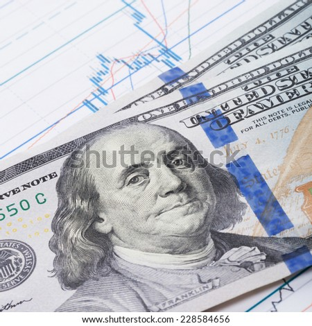 100 dollars banknote over stock market chart - studio shot - stock photo