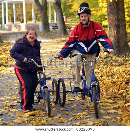 down syndrome couple on bicycles in the park - stock photo