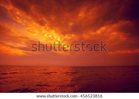 Dramatic red sunset over sea. Cloudy sky