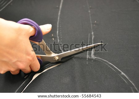 Dressmaker cutting fabric - stock photo