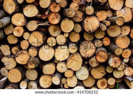 Dry chopped firewood logs in a pile - wood background. Saw timber prepared for winter heating season - stock photo