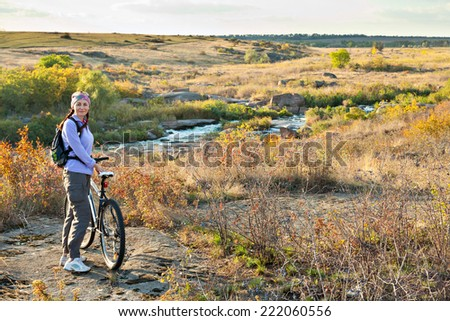 ��dult woman standing next to a mountain bike and looking at the camera on a river and hills background  - stock photo