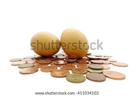 Egg  over many thai baht coins on a white background:select focus with shallow depth of field:Macro shot.