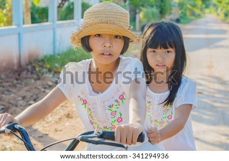 elder sister and younger sister and bicycle - stock photo