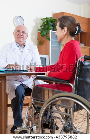 elderly doctor signing documents with   woman in   wheelchair.