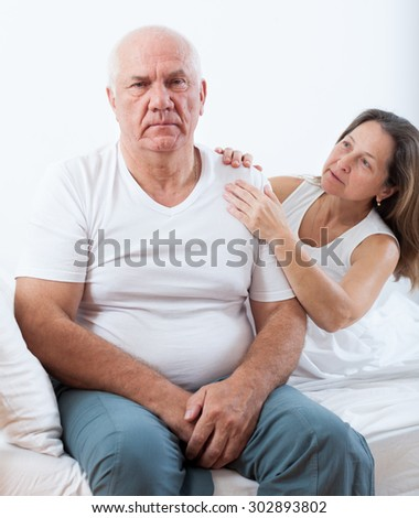 elderly man and   middle-aged woman sorting out their relationships   in   bedroom.
