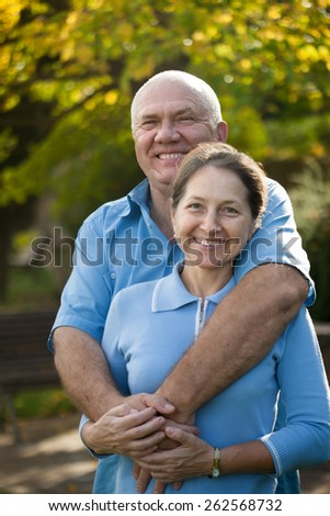 elderly woman and  senior man   walking in autumn park. - stock photo