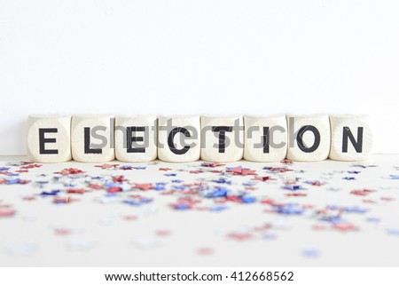 """ELECTION"" printed on eight white wood blocks against white background with confetti stars  - stock photo"
