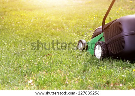 electric lawn mower on a green grass - stock photo