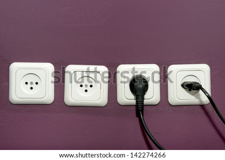 electrical power sockets and two plugs switched on - stock photo