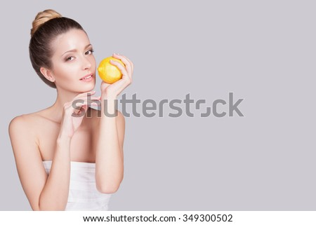 Elegant girl in profile, her head turned toward the camera, the woman grabbed a lemon yellow fingers holding it near the mouth. Horizontal photo with a slender girl on a gray background - stock photo