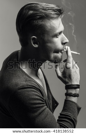 Emotive portrait of young fashionable model smoking  cigarette. Retro style. Close up. Black and white studio shot.