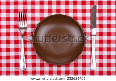 empty brown plate knife and fork on a checkered tablecloth - stock photo
