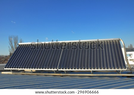 Energy  efficiency concept. Closeup of vacuum solar water heating system on the house  metal roof. - stock photo