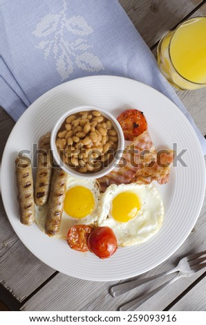 """English breakfast or a """"full English breakfast"""". Breakfast with fried eggs, bacon, sausages, beans, grilled tomato and orange juice. - stock photo"""