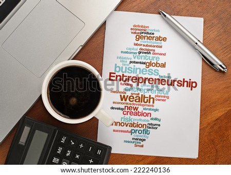 """ENTREPRENEURSHIP word cloud arrangement"" Notebook with text vision on table with coffee, calculator and notebook - stock photo"