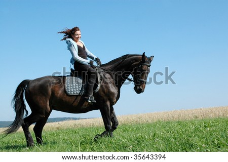 Equestrienne rides on the hillside. The  Hanoverian.