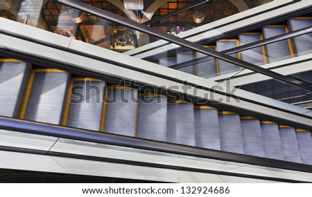 2 escalators cross going up and down in shopping mall for convenience of customers concept of progress and sale consumerism