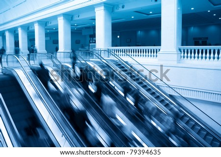 escalators in railway station with passenger motion blur