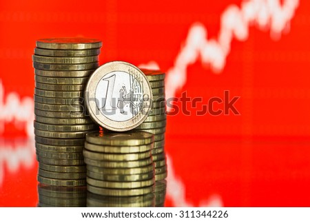 euro coin. Fluctuating graph on red background. Rate of the euro (shallow DOF)  - stock photo