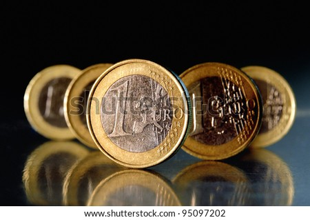 1 Euro coins in front of black background - stock photo