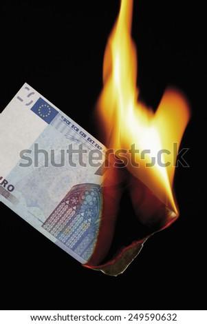 20 euro note burning against black background - stock photo