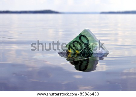 100-euro note sinking into the water, shot on a lake - stock photo