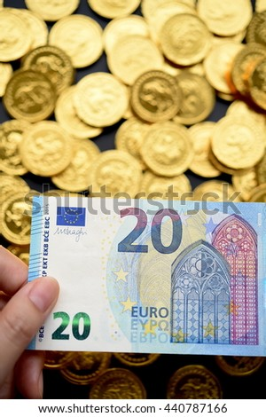 20 Euro on hand and gold coins for background