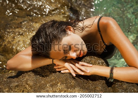 Exotic beautiful brunette with wet look and bright makeup by the sea. Golden reflection.Toned in warm colors. horizontal shot, outdoors - stock photo