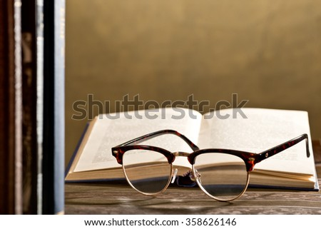 eyeglasses and books on the table - stock photo