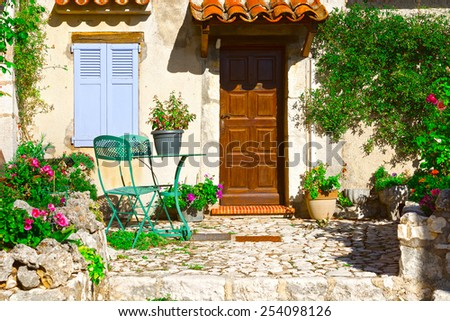Facade of French House with Door and Window Decorated with Fresh Flowers - stock photo