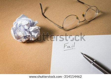 """""""Fail"""" hand writing on paper, glasses pen and crumpled paper. Business frustrations, Job stress and Failed exam concept. - stock photo"""