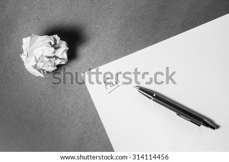 """""""Fail"""" hand writing on paper, pen and crumpled paper. Business frustrations, Job stress and Failed exam concept. Black and white filter. above shot. - stock photo"""