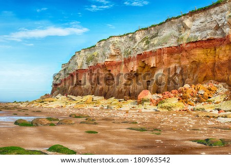 Fallen rocks onto beach from cliff face - stock photo