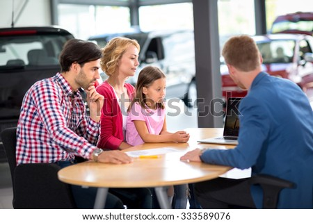 Family  interested in purchasing new car listens car agent in car showroom - stock photo