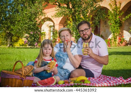 Family picnic sitting on green grass, smiling family, lovely blonde daughter, beautiful mother, bearded father.
