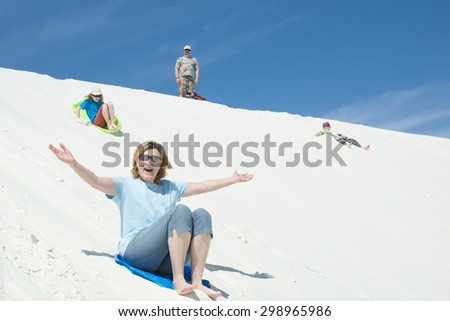 Family sledding, digging sand on a sand dune in White Sands National Monument, New Mexico - stock photo
