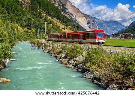 Famous electric red tourist train in Tasch,Valais region,Switzerland,Europe - stock photo