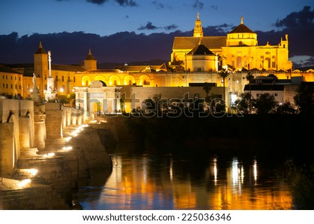 Famous Mosque (Mezquita) and  Roman Bridge at night with illuminations, Cordoba, Andalusia, Spain, Europe - stock photo