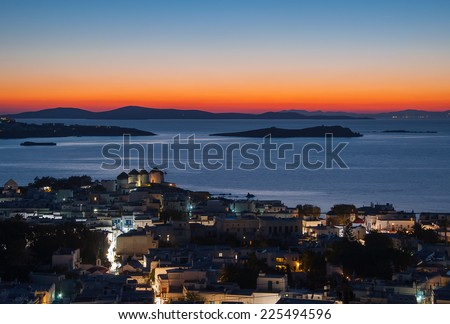 5 famous windmills of Mykonos on the background of the night in the lights of the town and the sea. - stock photo