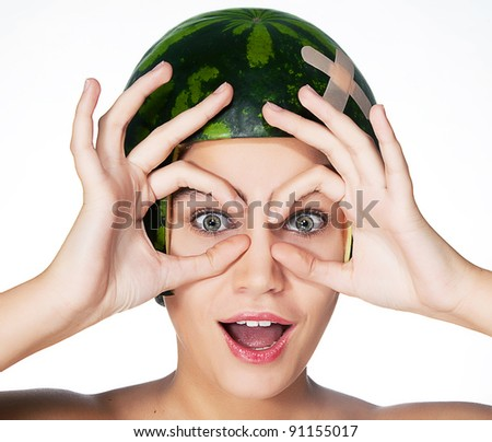 Fancy young girl with fresh watermelon as a helmet on her head. Series of photos - spyglass