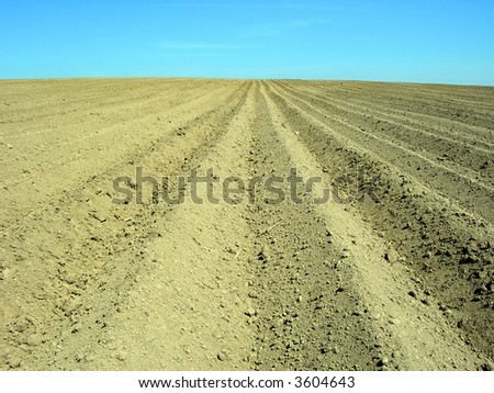 Farmland cultivated by plough after the harvest - stock photo