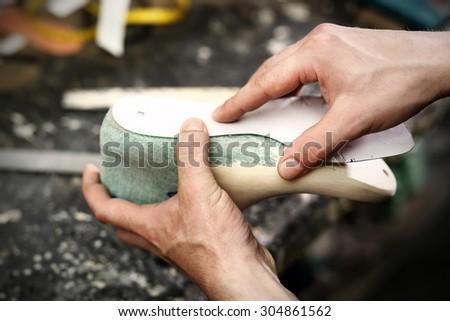 Fashion and shoe design, workshop.Shoemaker sews shoes - stock photo