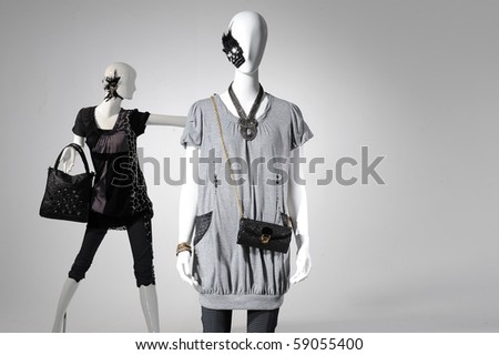 Fashion clothes on a mannequin holding bag on light background - stock photo