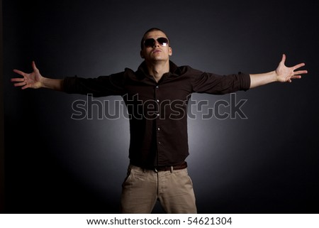 fashion picture of a man standing on a dark background with his hands to sides - stock photo